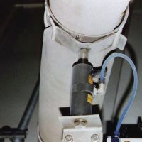 Problem: Fine material was building up on the walls of a fill tube.  Solution: An NTK<SUP>®</SUP> 25 AL Oscillator, operated by a timer, taps on the pipe, 5 seconds/ minute, eliminating the build-up.